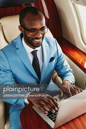 Smiling male entrepreneur working on laptop in private jet - p300m2257046 by OneInchPunch