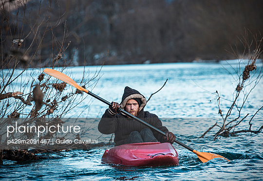 Young man kayaking on river in winter, portrait, Domodossola, Piemonte, Italy - p429m2091467 by Guido Cavallini