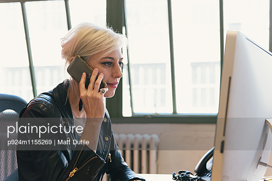 Woman at desk using smartphone to make telephone call
