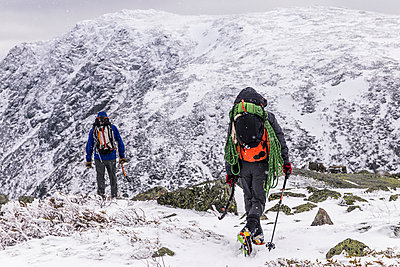 Rear view of backpackers standing on snowcapped Mountain during winter - p1166m1566944 by Cavan Images