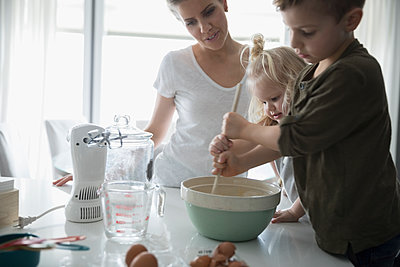 Mother and children baking in kitchen - p1192m1231355 by Hero Images