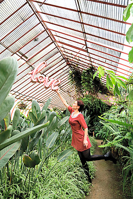 Woman in pink dress in a greenhouse holding a balloon with the lettering love - p1521m2228335 by Charlotte Zobel