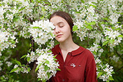 Young woman between blooming bush, portrait - p1646m2264059 by Slava Chistyakov