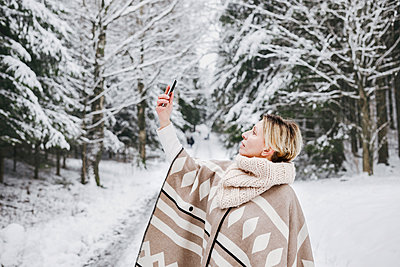 Mature woman in warm clothing taking selfie through smart phone in snow - p300m2256102 by Katharina Mikhrin