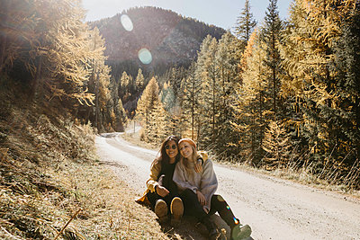 Smiling friends sitting on footpath in forest - p300m2267129 by letizia haessig photography