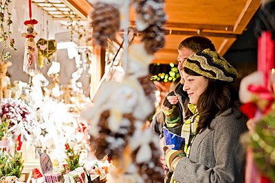Germany, Berlin, young couple watching offerings at Christmas market - p300m911127f by Claudia Paulussen
