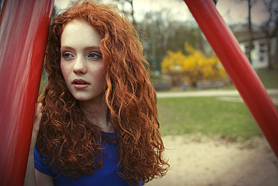 Portrait of girl with curly red hair on a playground - p300m982242f by Gabi Dilly