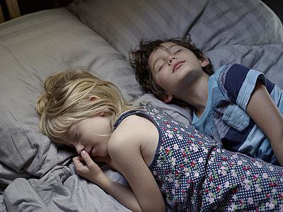 Two children sleeping on bed - p945m1480831 by aurelia frey
