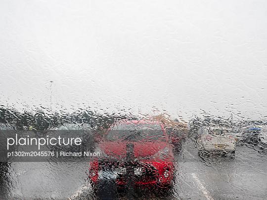 Blick durch verregnete Windschutzscheibe auf Autos  - p1302m2045576 von Richard Nixon