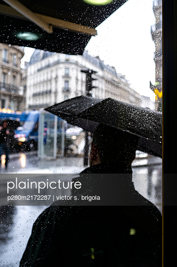 Mann mit einem Regenschirm in der Stadt - p280m2172287 von victor s. brigola