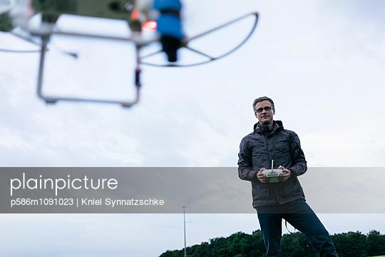 Man operates quadrocopter using remote control - p586m1091023 by Kniel Synnatzschke