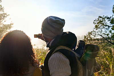 Young couple hiking and using camera phone in sunny woods - p1023m2212840 by Trevor Adeline