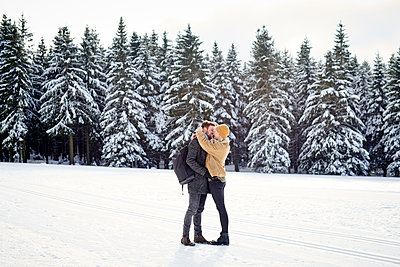 Young couple kisses in snowy landscape - p1124m1589311 by Willing-Holtz