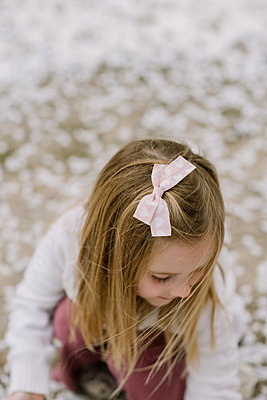 Preschool girl looking down at ground outside - p1166m2191787 by Cavan Images