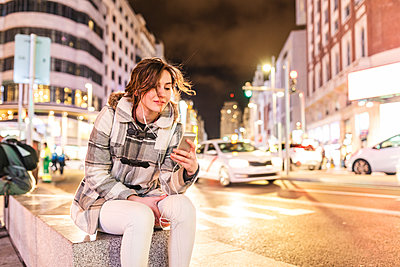 Spain, Madrid, young woman in the city at night using her smartphone and wearing earphones - p300m2104617 von William Perugini