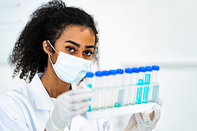 Female researcher in protective face mask holding test tubes at laboratory - p300m2266233 by Giorgio Fochesato