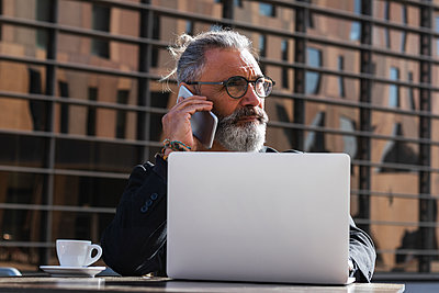 Bearded businessman talking on mobile phone while sitting in cafe - p300m2276279 by NOVELLIMAGE