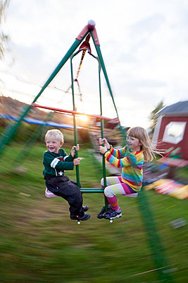 Boy and girl swinging, Norrbotten, Sweden - p312m926981f by Fredrik Ludvigsson