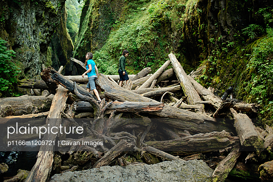 Couple walking on logs amidst rock formations in forest - p1166m1209721 by Cavan Images