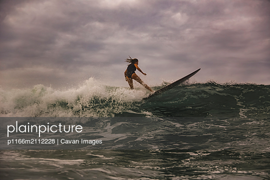 Young woman surfing at sunset - p1166m2112228 by Cavan Images