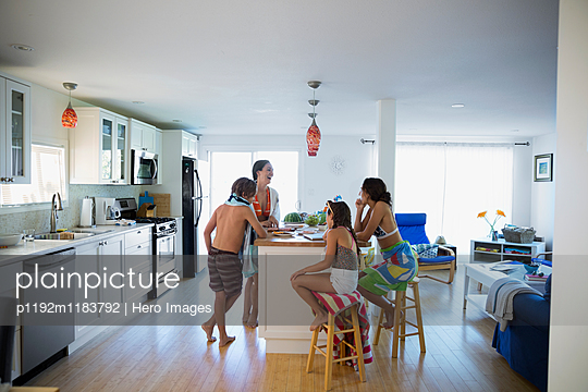 Family in bathing suits at kitchen island - p1192m1183792 by Hero Images