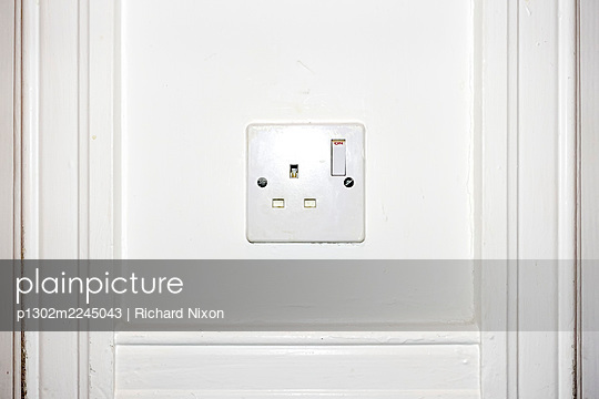 Old british electricity socket on a white wall - p1302m2245043 by Richard Nixon