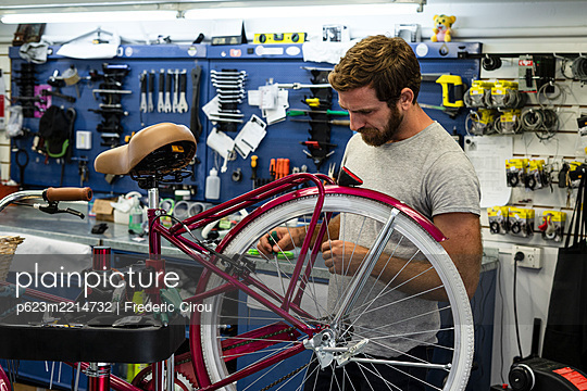 Mechanic repairing bicycle in workshop - p623m2214732 by Frederic Cirou