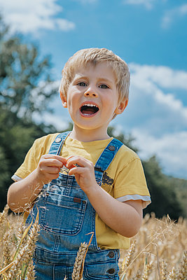 Cute boy with mouth open standing in barley field - p300m2276239 by Mareen Fischinger