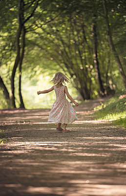Little girl dancing on forest track - p300m948996 by Martin Wimmer