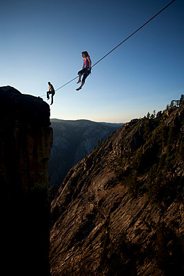 Female highliners simultaneously sitting on a highline above the Yosemite Valley floor at Taft Point - p343m1003015f by Jared Alden