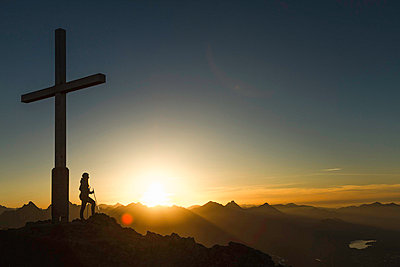 Hiker standing by cross on rocky hilltop - p429m756503 by Manuel Sulzer