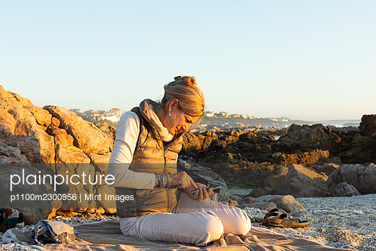 An adult woman sitting on the beach using her smart phone at De Kelders at sunset. - p1100m2300956 by Mint Images