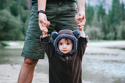 Midsection of father holding daughter's hands while standing by lake at Yosemite National Park - p1166m2000748 by Cavan Images