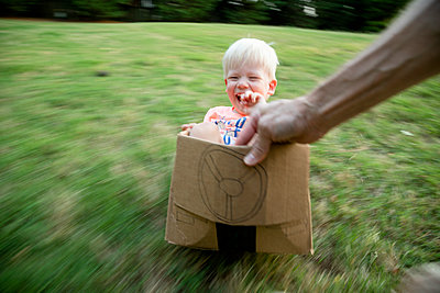 A father pulls his excited son in a cardboard car across their backyard - p1480m2148194 by Brian W. Downs