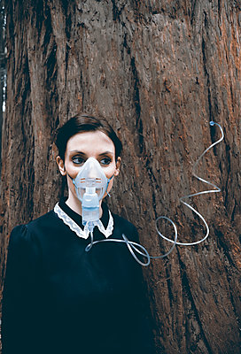 Woman with oxygen mask plugging into a tree - p1521m2228363 by Charlotte Zobel
