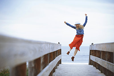 Woman on a wooden pier looking to the ocean - p1577m2150306 by zhenikeyev