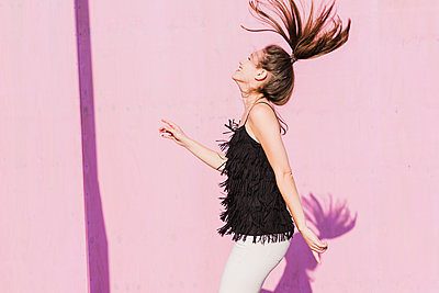 Happy young woman moving in front of pink wall - p300m2059414 by Uwe Umstätter