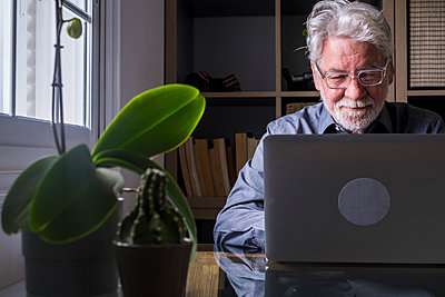 Male entrepreneur working on laptop at home - p300m2276589 by Simona Pilolla