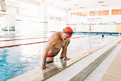 Senior man climbing up side of swimming pool - p429m1469466 by Eugenio Marongiu