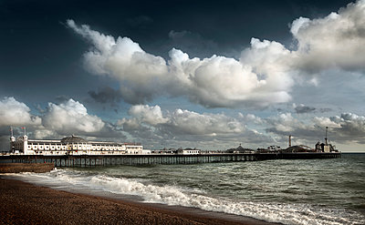 Clouds over boardwalk and beach, Brighton, Sussex, England - p555m1454228 by Chris Clor