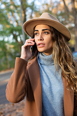 Young woman using smartphone outdoors - p975m2222121 by Hayden Verry
