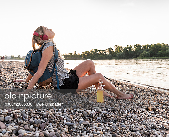 Blond woman with earphone and bottle sitting on riverside in the evening, listening music - p300m2005336 von Uwe Umstätter