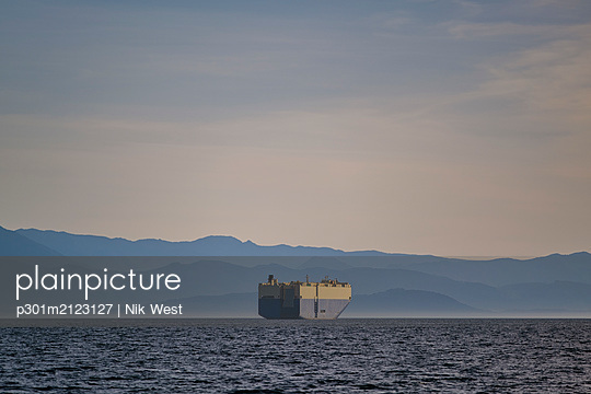 Container ship on sunny, idyllic ocean with Olympic Mountain Range in background - p301m2123127 by Nik West