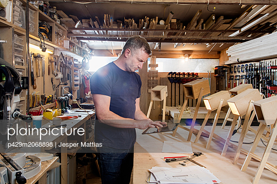 Designer using digital tablet by prototypes of table lamps - p429m2068898 by Jesper Mattias