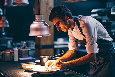 Cook serving food on a plate in the kitchen of a restaurant - p300m2144262 von Oscar Carrascosa Martinez