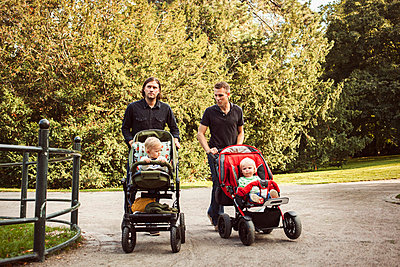 Men pushing babies on baby carriages in park - p426m977525f by Astrakan