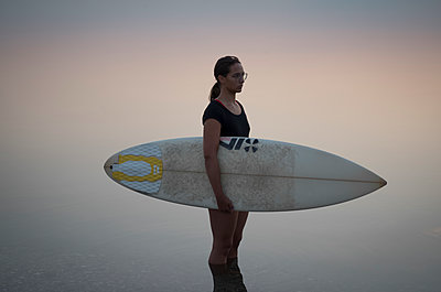 Young woman carrying surfboard - p552m2020170 by Leander Hopf