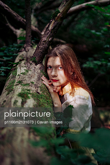 portrait of a woman in a forest standing near a tree - p1166m2131073 by Cavan Images
