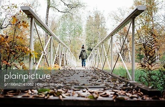 boy walking along a bridge with autumn leaves in fall in the forest - p1166m2141082 by Cavan Images