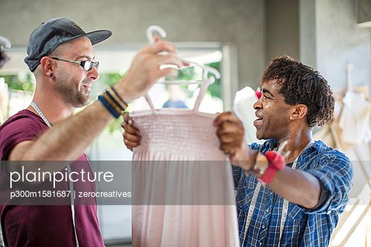 Smiling fashion designer showing dress to colleague - p300m1581687 von zerocreatives